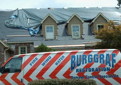 Burggraf van in front of a house with tarp over the roof